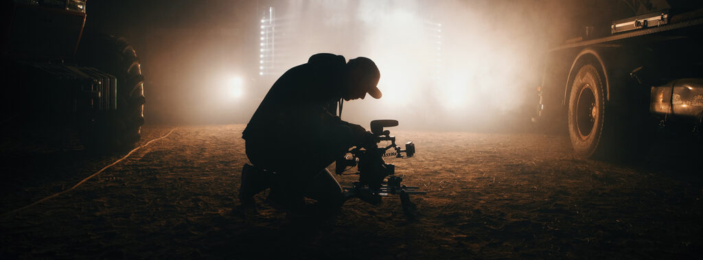 A man operates a video camera against a backlight. Photograph by Jon Flobrant.